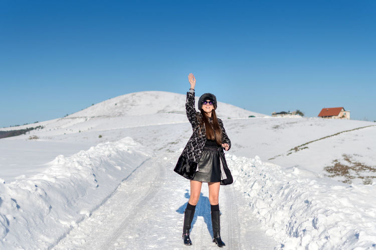 One Person Snow Young Adult Sky Lifestyles Winter Young Women Leisure Activity Beauty In Nature Real People Cold Temperature Blue Front View Nature Standing Full Length Clear Sky Clothing Hair Warm Clothing Human Arm Outdoors Hairstyle