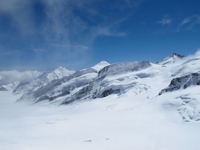 Scenic view of snowy mountains against blue sky