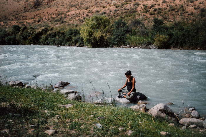 YOUNG MAN SITTING ON ROCK BY LAKE
