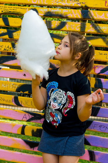 Girl Eating Cotton Candy While Standing Against Wall