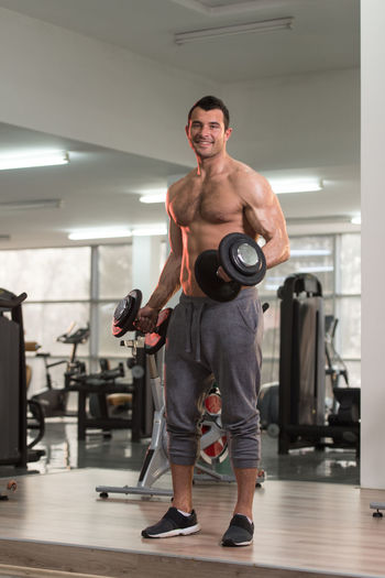 Portrait of shirtless young man exercising in gym
