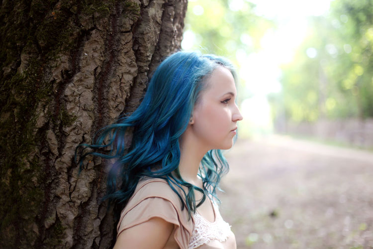 Close-up of beautiful young woman against tree trunk