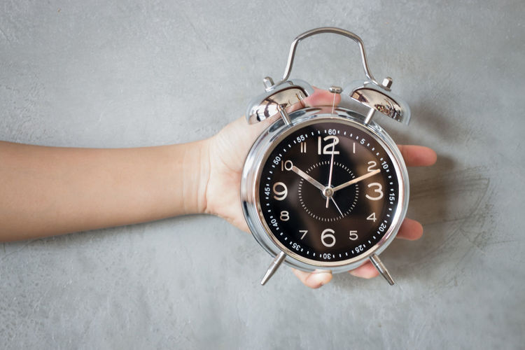 Close-up of human hand holding alarm clock against wall