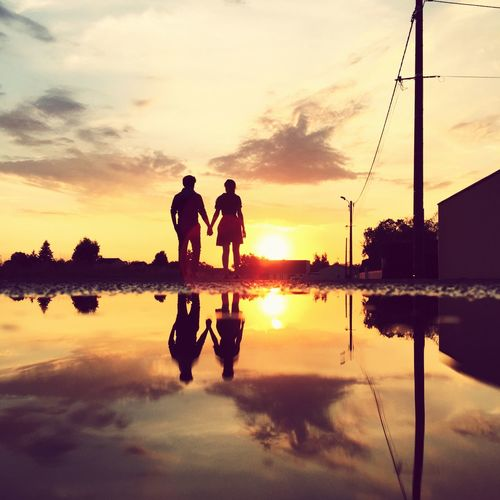 Silhouette people holding hands while standing against sky at sunset