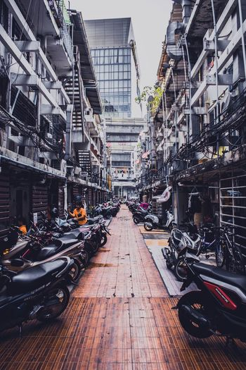 Motorcycles Parked Amidst Buildings In City