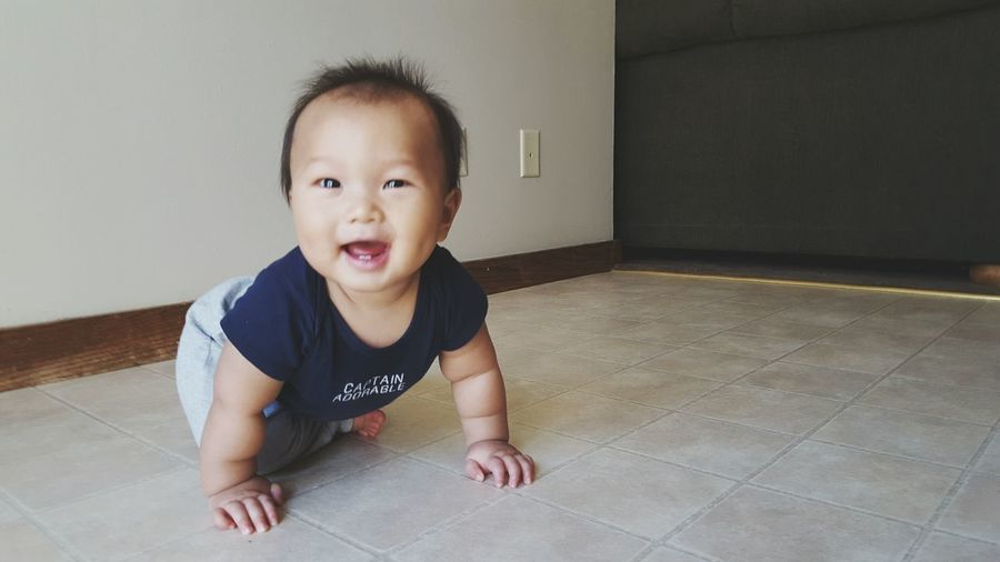 Portrait Of Happy Boy On Floor At Home