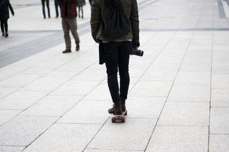 Low Section Of Person With Camera Skateboarding On Footpath