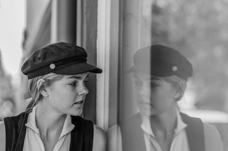 Young woman peeking through window