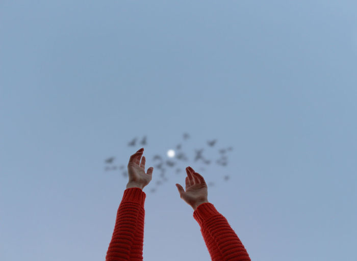 Low angle view of woman flying against clear sky