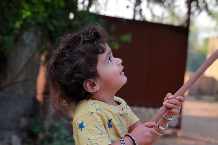 Profile view of a little child holding a wooden stick and looking at it