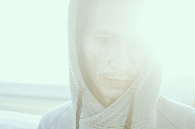 Close-up of man wearing hooded shirt during sunny day