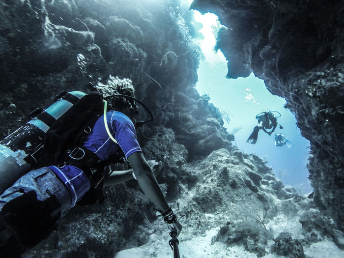 Low angle view of people scuba diving underwater by rock formation