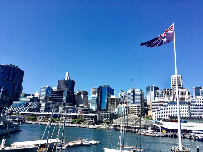 Low angle view of buildings and australian flag against clear blue sky