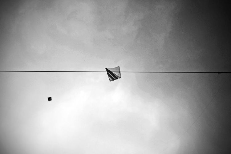 Low Angle View Of Kite Stuck On Cable Against Sky