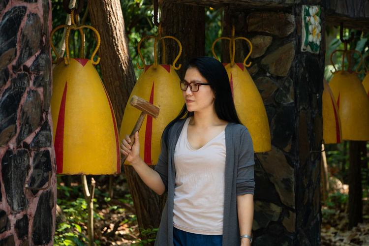 Woman knocking bell in Thai buddhist temple : Buddist Temple Buddhist Buddhism Bell Hitting Faith Religion Chime Outdoors Contemplation Beautiful Woman Day Standing Three Quarter Length Front View Casual Clothing One Person Leisure Activity Asian  Thailand Young Adult Hairstyle Lifestyles