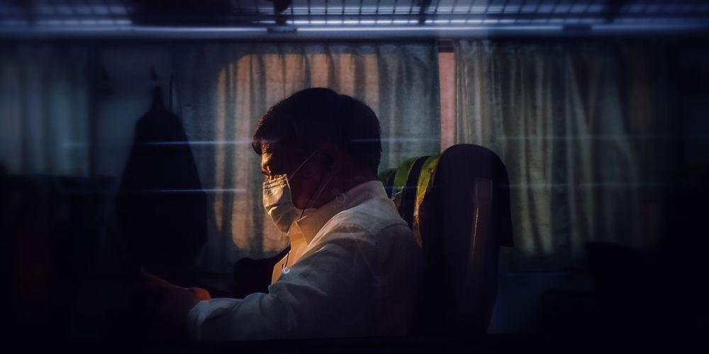Side view of man sitting on window