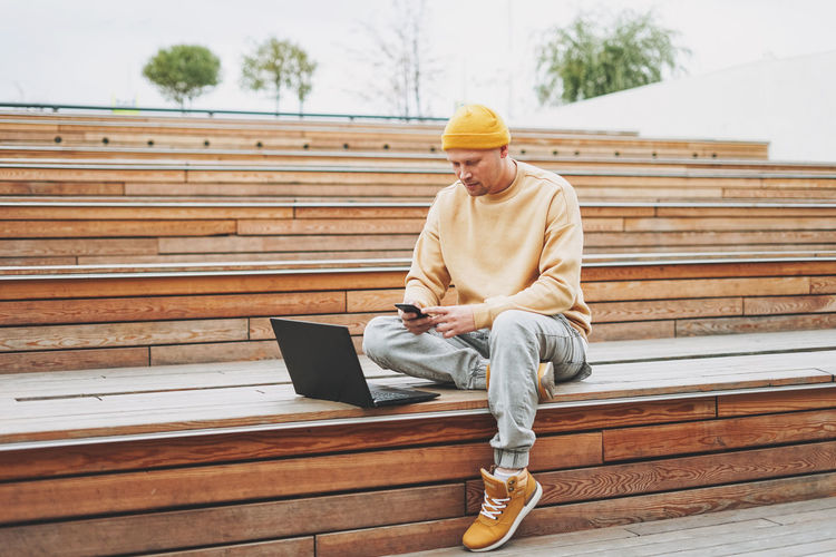 Full length of man using smart phone while sitting on steps outdoors