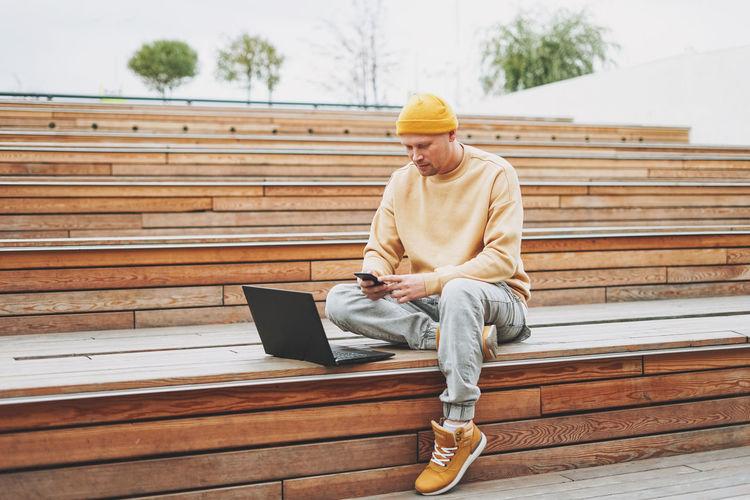 Full length of man sitting on bench