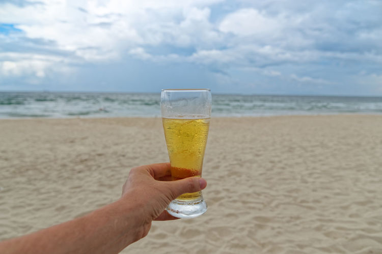 Man drinking glass on beach
