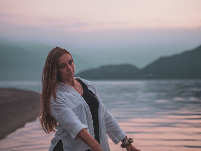 Portrait of young woman standing in sea against sky during sunset