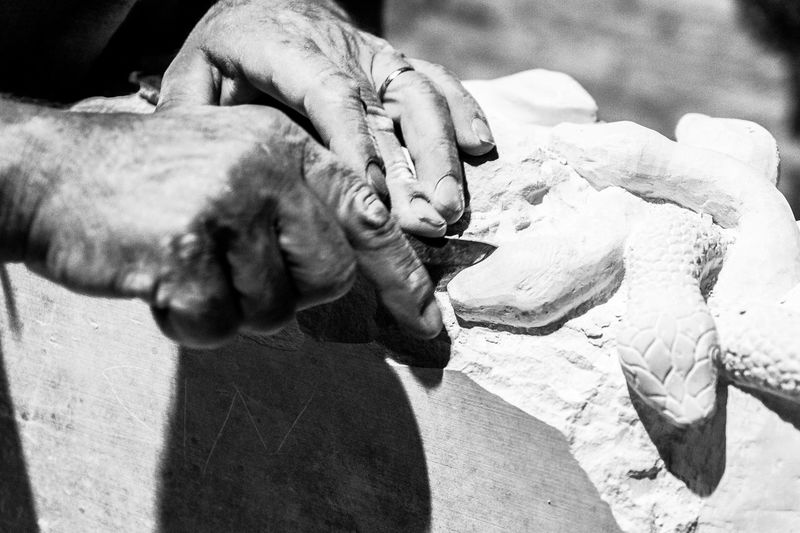 Cropped hands of male worker carving snake sculptures on stone