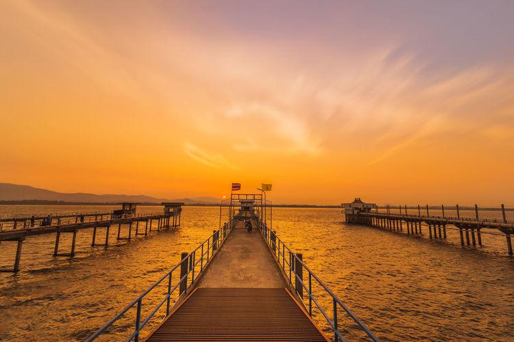 Pier over sea against orange sky
