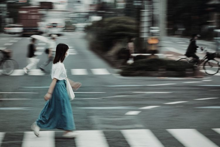 Blurred motion of woman walking on road