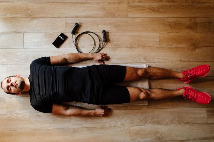 Man lying down on hardwood floor