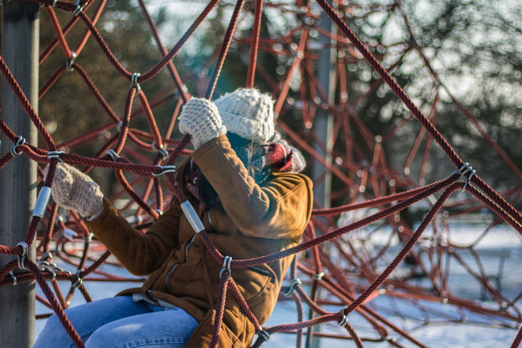 Woman sitting on ropes at snow covered park