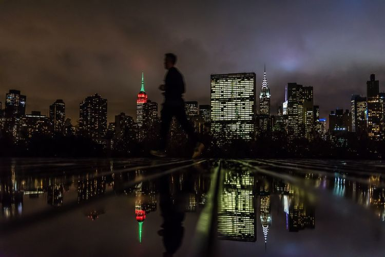 Side view of man jogging on wet footpath with reflection against illuminated skyline