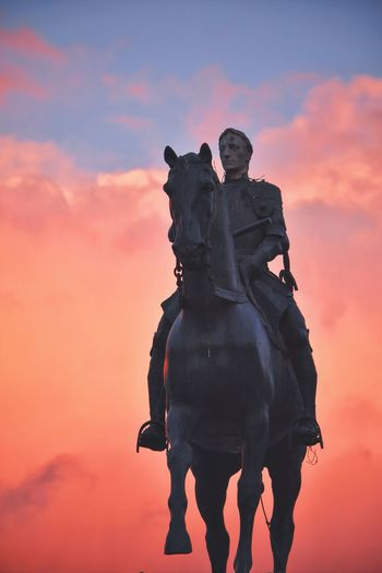 Low Angle View Of Historic Statue Against Orange Cloudy Sky