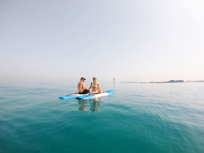 Active couple on the paddle boards with a view on burj al arab