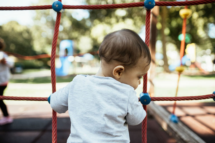 Boy playing on rope in playground