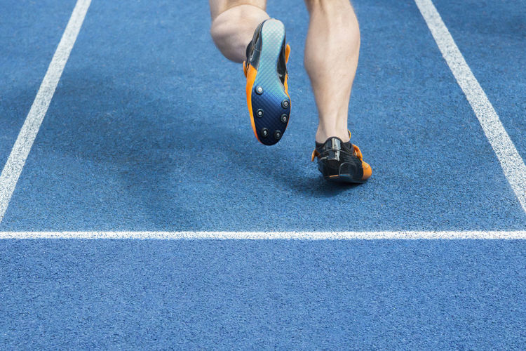 Low section of male athlete running on track