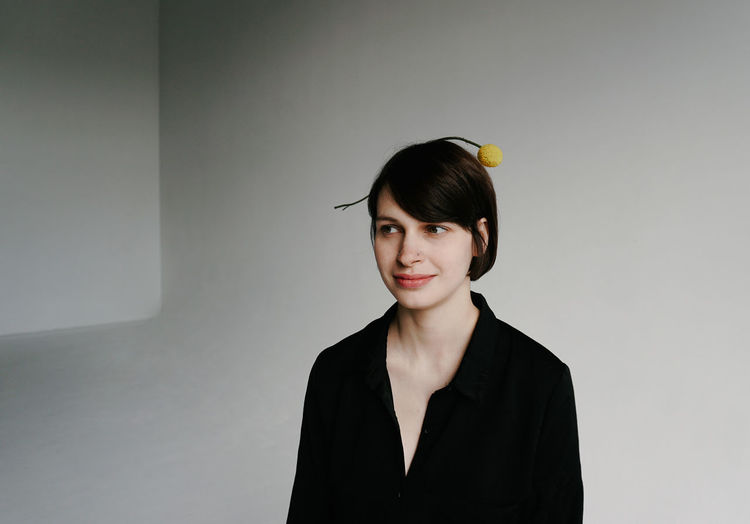 One Person Portrait Young Adult Indoors  Young Women Smiling Adult Looking At Camera Front View Headshot Real People Hairstyle Bangs Beautiful Woman Women Casual Clothing Gray Background Gray Studio Shot Lifestyles Portrait Of A Woman Thoughtful Beautiful Minimalist Minimalism Plant