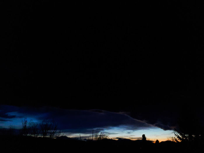 Silhouette landscape against sky at night