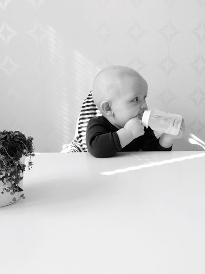 Baby boy drinking water while sitting at table against wall at home