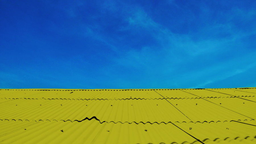 Low angle view of yellow lines against blue sky