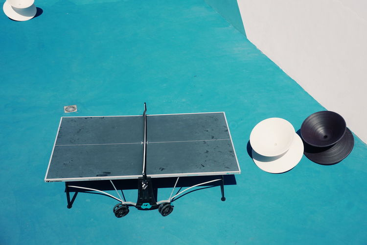 High angle view of empty table tennis at court during sunny day