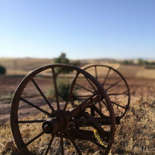 Close-up of rusty wheel on field against clear sky