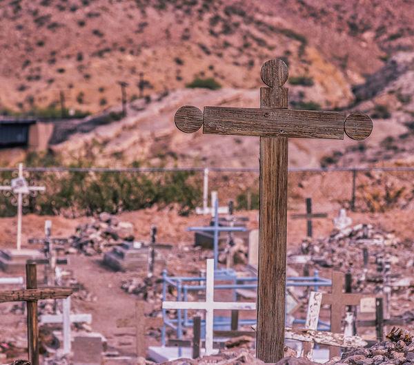 Cross on cemetery against temple