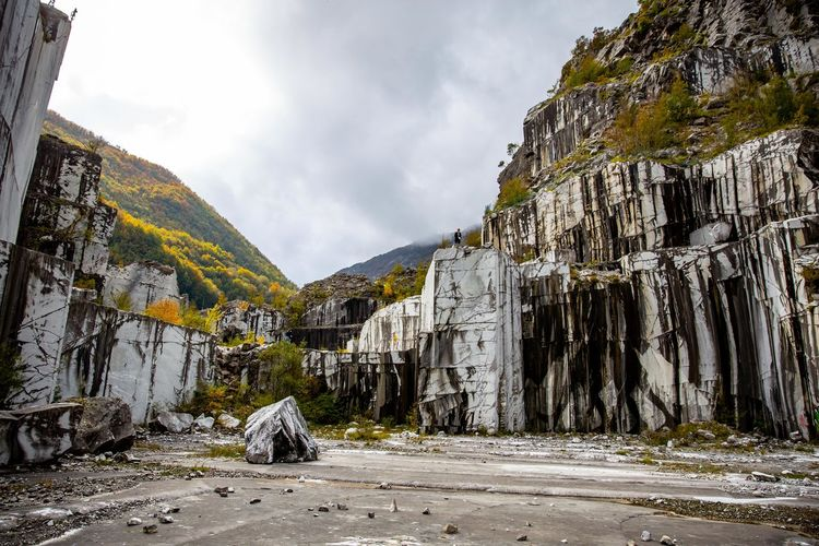 Carrara marble mine with unique patters and fall trees in italy.