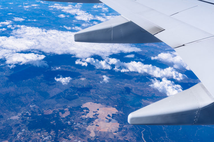 Aerial view of clouds over airplane wing