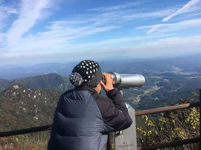 Man looking through hand-held telescope on mountain against sky