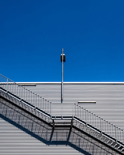 Low Angle View Of Street Light Against Building Against Clear Blue Sky
