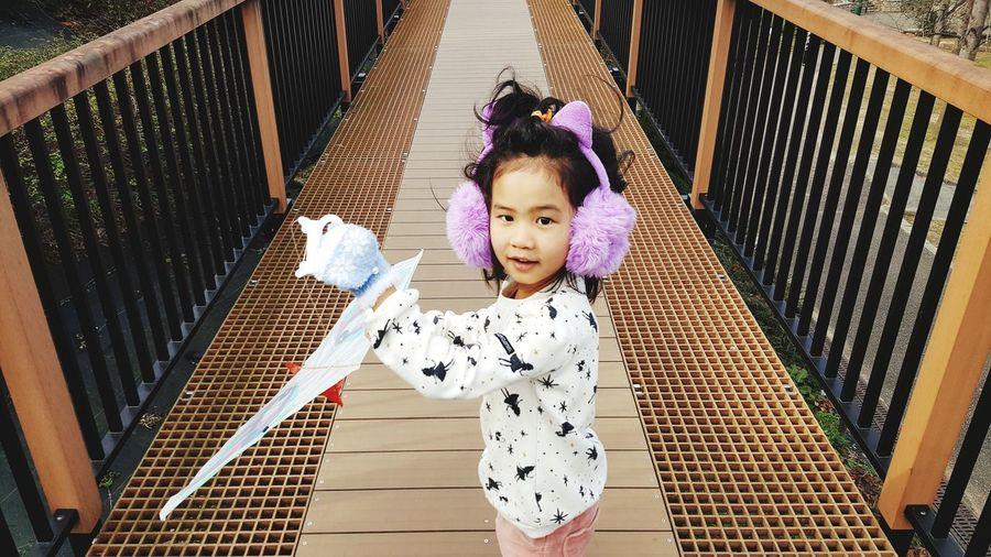 Portrait of cute girl with kite standing on footbridge