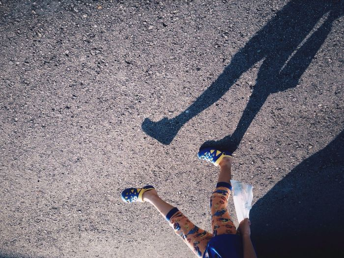 Low Section Of Child Walking On Street With Shadow