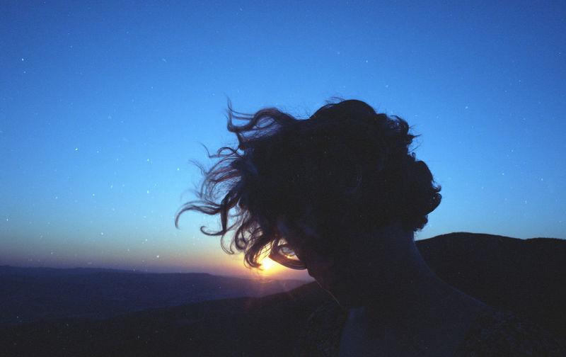 Portrait of silhouette woman against blue sea