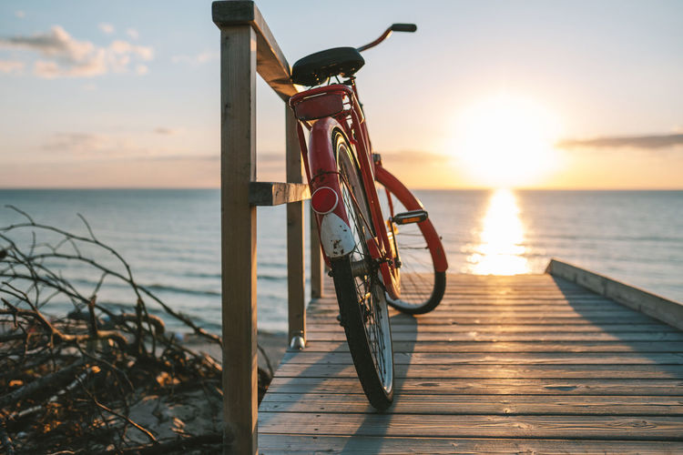 Bicycle on beach against sky during sunset