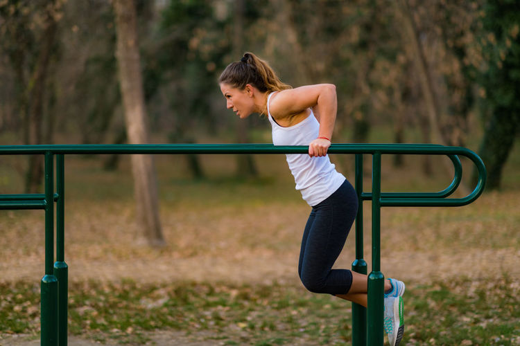 Side view of woman exercising on bars in park